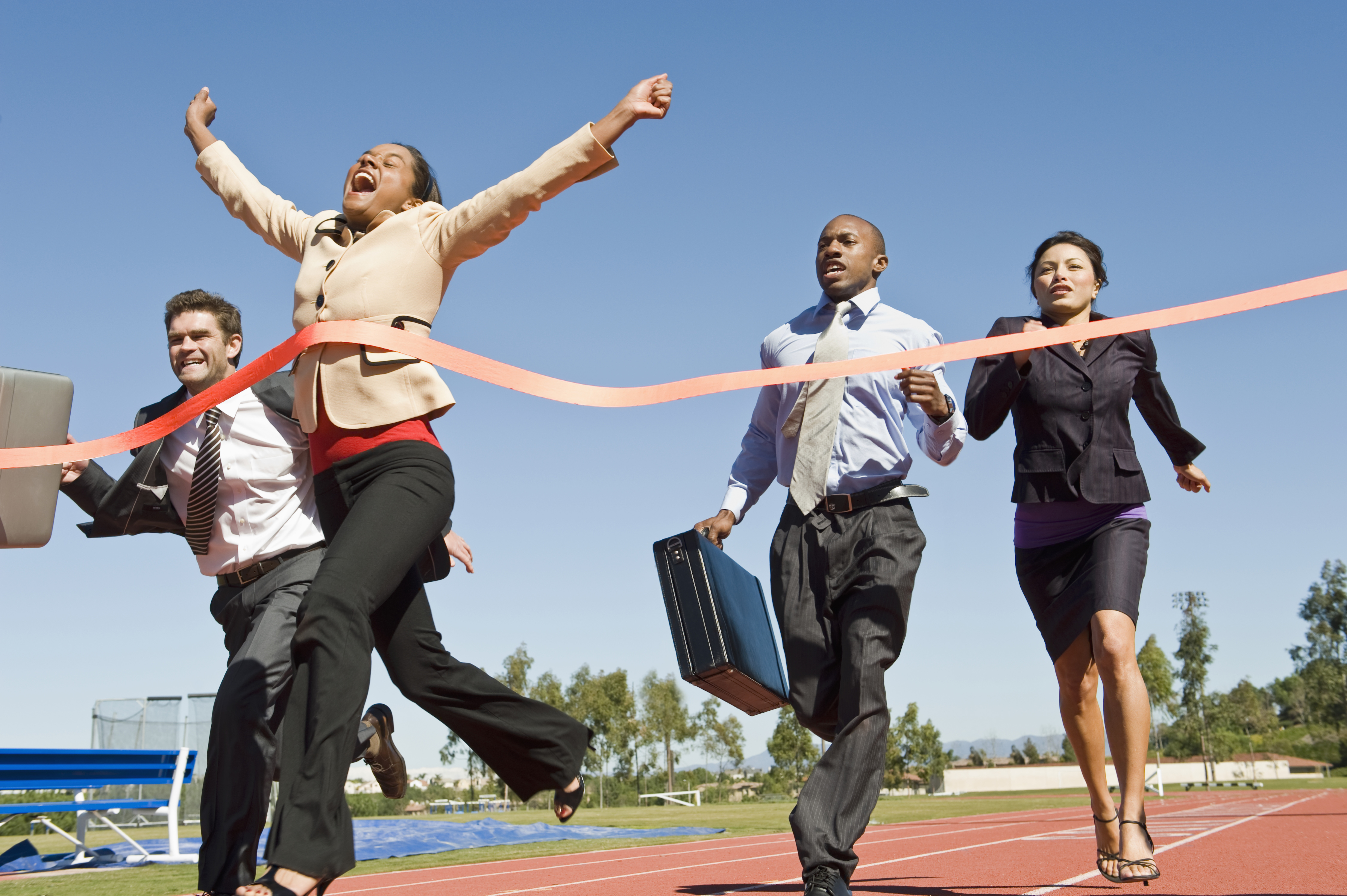 Motion blur shot of a cheerful business woman crossing the finish line (shutterstock_122081617)